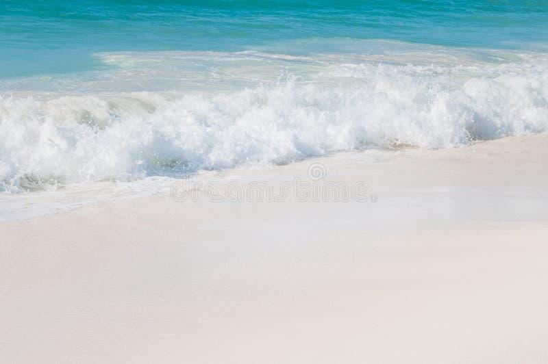 Mare del turchese con le onde di bianco e la sabbia bianca fotografia stock