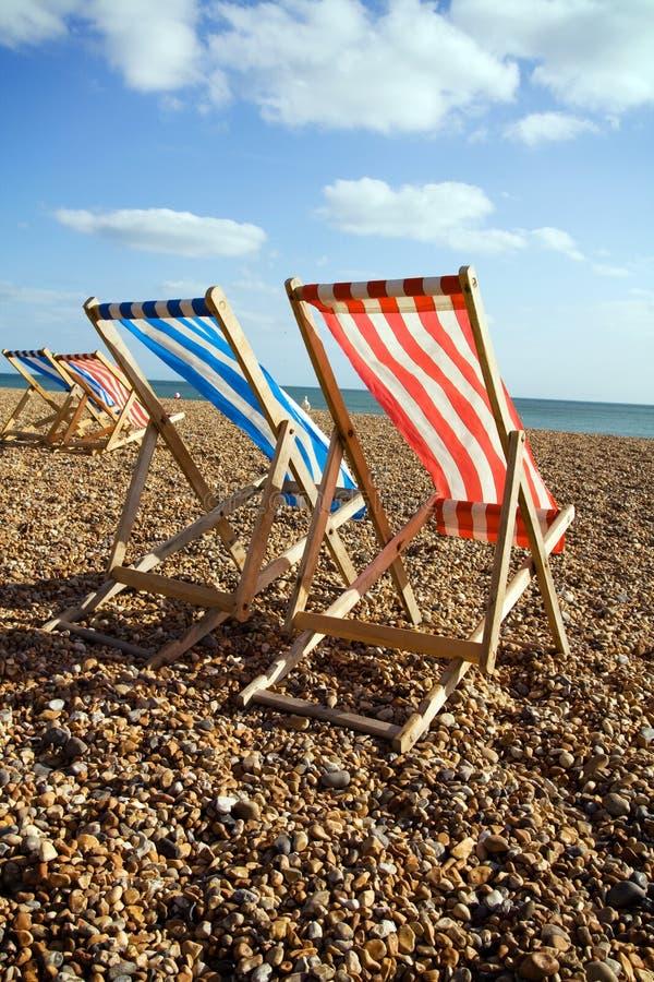 Mare della spiaggia di Deckchairs ventoso fotografie stock
