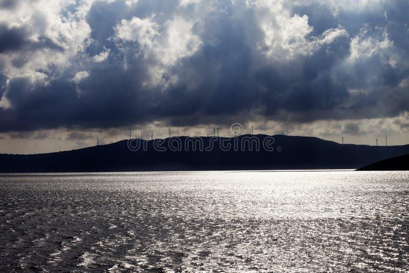 Mare di luce solare, parco eolico sulle montagne e cielo nuvoloso prima della tempesta fotografia stock