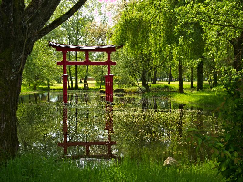 Mare, greenery and Asian decor in a park of Vesoul in France with reflections in the water stock photography