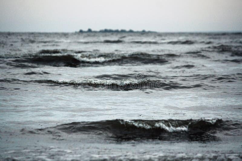 Mare grigio nella pioggia con i grandi wawes immagini stock