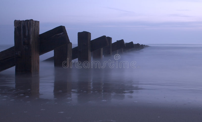 Mare, pali e tramonto immagini stock