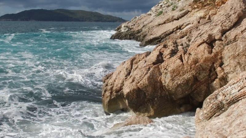 Mare puro delle acque blu, onde costiere che rompono e che spruzzano avventura sulle rocce della spuma della costa di mare metrag immagini stock