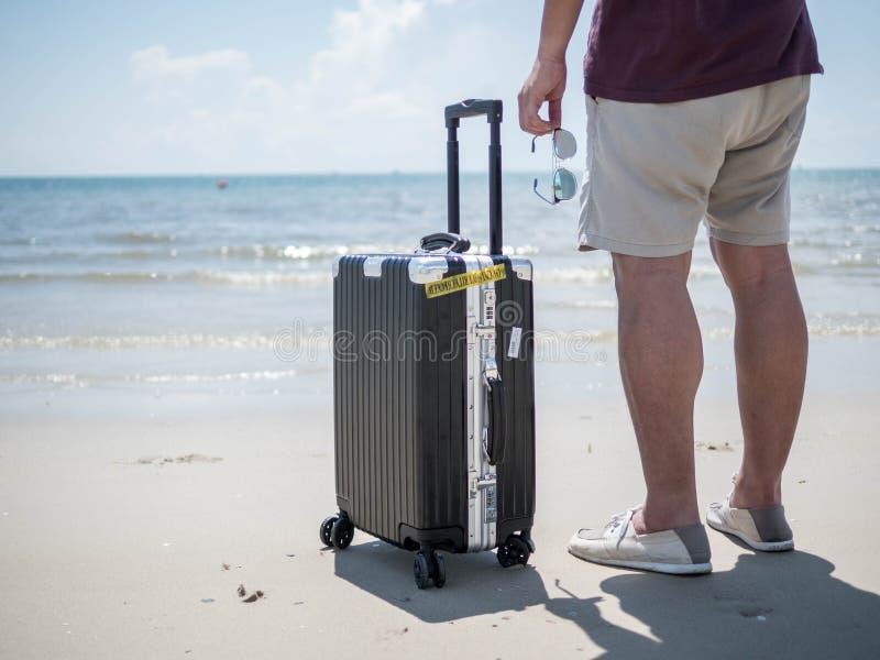 Mare tropicale, condizione del giovane che tiene gli occhiali da sole con la borsa di viaggio alla spiaggia Progettazione di mass fotografie stock