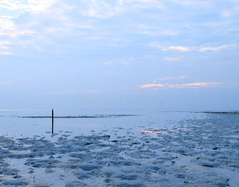 Marea baja en la playa - infinito en el horizonte y el cielo nublado en el amanecer - paz, calma, y tranquilidad foto de archivo libre de regalías