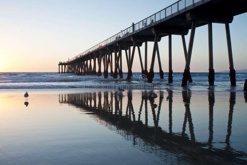 Marea inferior de la puesta del sol del embarcadero de la playa de Hermosa fotografía de archivo libre de regalías