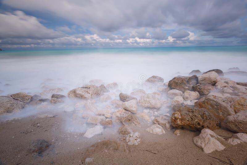 Maree ricevute su una spiaggia rocciosa sotto i cieli tempestosi fotografie stock libere da diritti