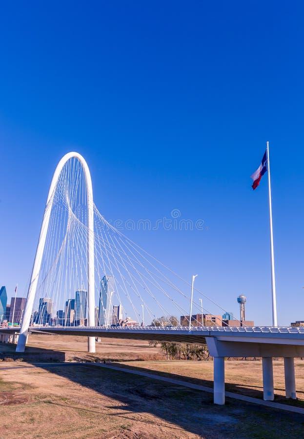 Margaret Hunt Hill Bridge con la bandera de Tejas y horizonte de Dallas en el fondo foto de archivo