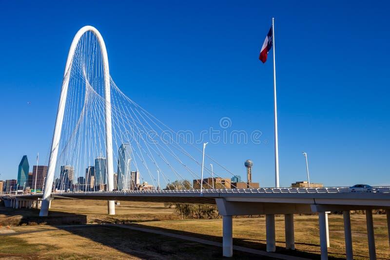 Margaret Hunt Hill Bridge met de vlag van Texas en de horizon van Dallas op de achtergrond royalty-vrije stock afbeeldingen