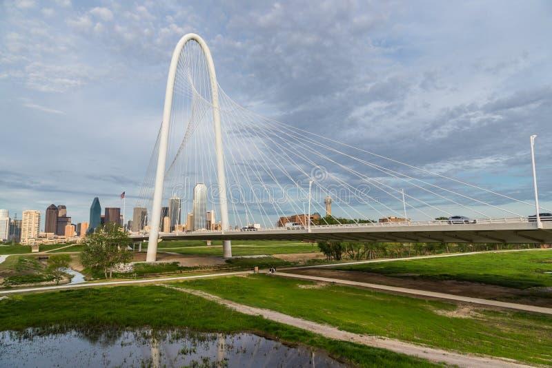 Margaret Hunt Hill Bridge och Dallas i stadens centrum horisont royaltyfri fotografi