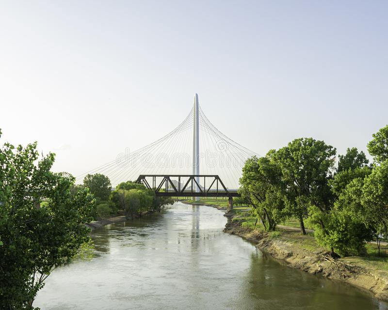 Margaret Hunt Hill and Railroad Trestle Bridge over Trinity River. A picture of the Margaret Hunt Hill Bridge with a Railroad Trestle Bridge in the foreground stock image