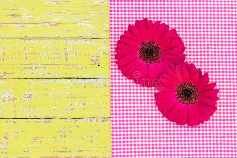 A margarida cor-de-rosa do gerbera floresce na tela quadriculado cor-de-rosa e na madeira rústica, vista superior imagens de stock royalty free
