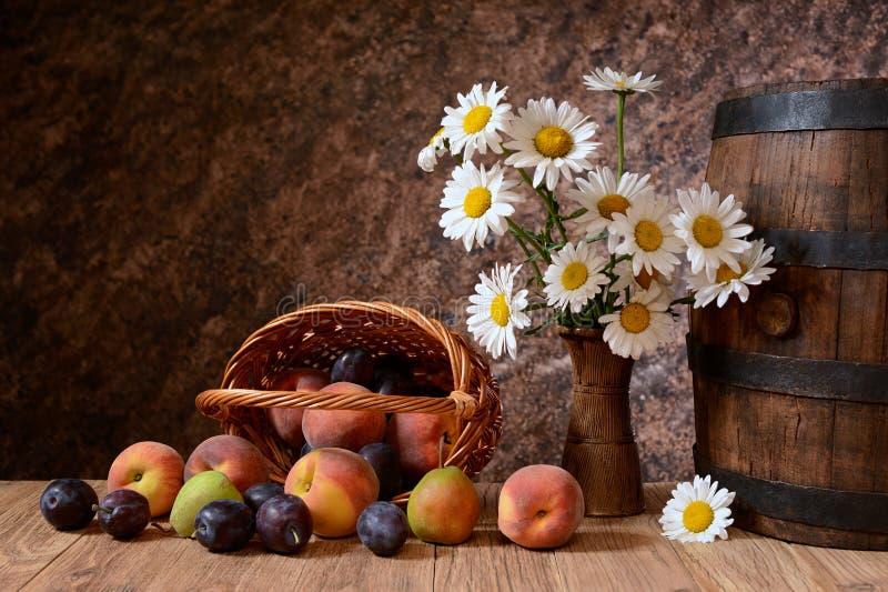 A margarida floresce em um vaso com frutos frescos em uma cesta do vicker imagens de stock