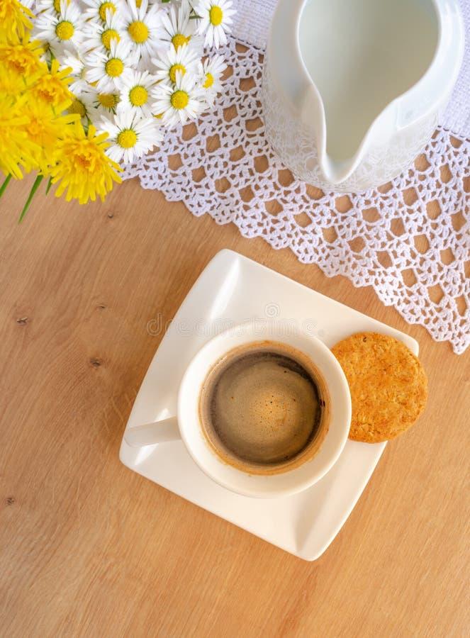 Margaridas e dentes-de-leão, uma xícara de café e uma cookie em uma tabela de madeira imagens de stock
