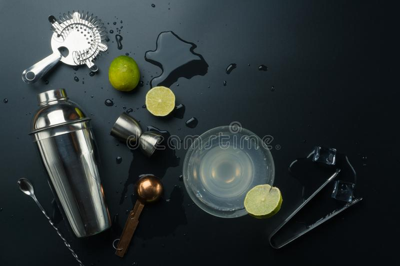Margarita cocktail and bar equipments. Stainless steel cocktail shaker and jigger, copper measuring spoon, bar spoon with strainer, the lemons and ice tongs royalty free stock photo