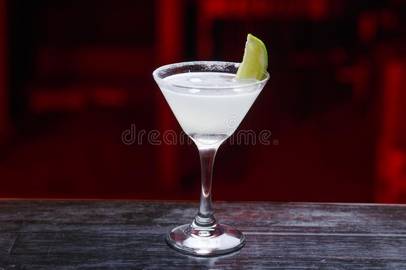 Close up of a cocktail with lime and salted rim, standing on the bar counter, isolated on a red light background. stock photo