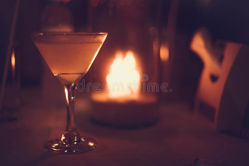 Margarita iced cocktail in martini glasses in front of the night bokeh lights on blurred candle background royalty free stock photo