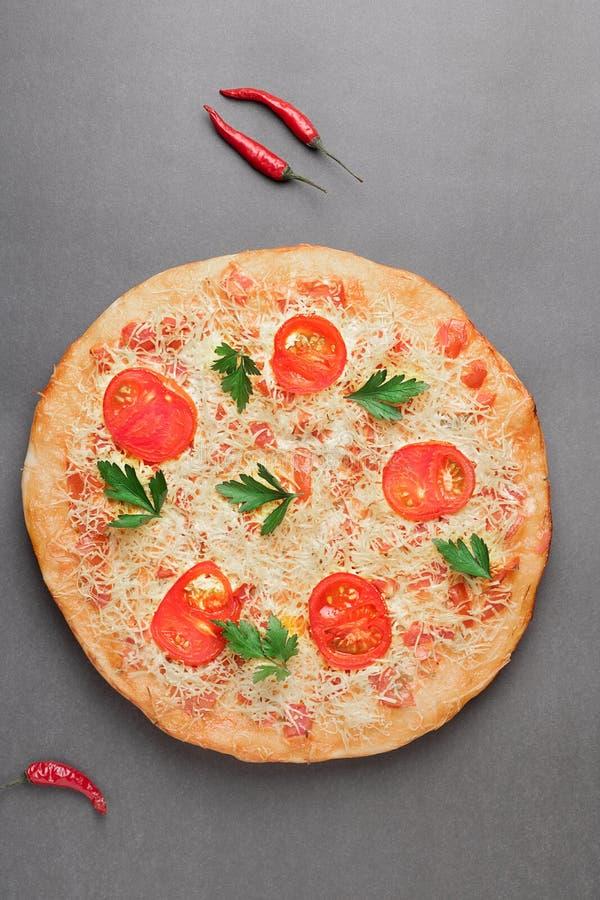Margarita Pizza met tomaat en rode Spaanse peper twee op grijze lijst, hoogste mening en plaats voor tekst stock fotografie