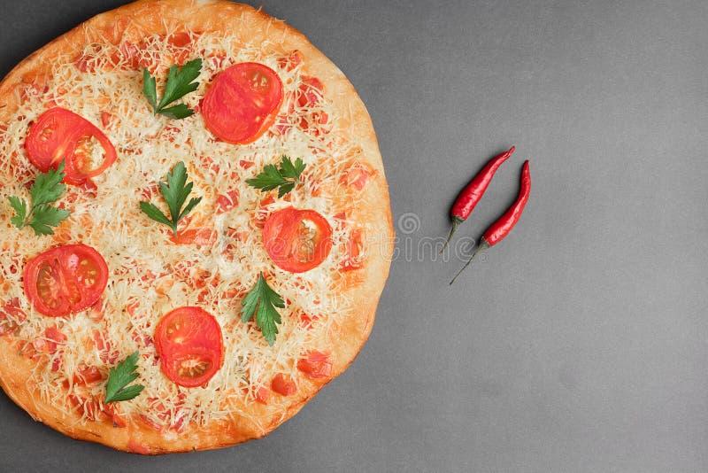 Margarita Pizza met tomaat en rode Spaanse peper twee op grijze lijst, hoogste mening en plaats voor tekst stock foto's
