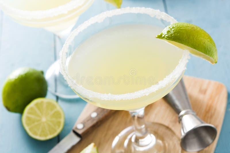 Margaritacoctailar med limefrukt i exponeringsglas på den blåa trätabellen arkivfoto