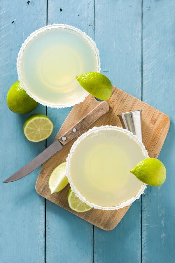 Margaritacoctailar med limefrukt i exponeringsglas på den blåa trätabellen arkivbild