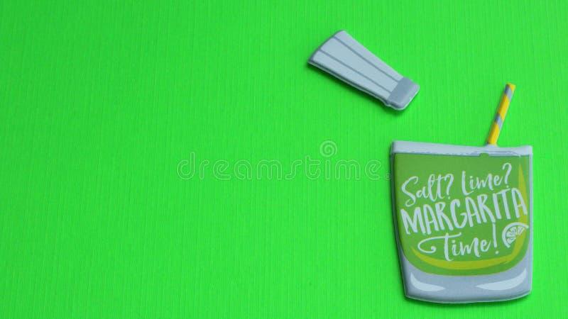 Margaritaexponeringsglas med sugrör på en grön bakgrund