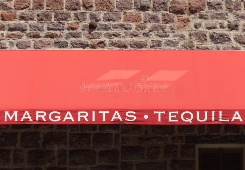 Margaritas at the saloon. Margaritas and tequila, signage on a sidewalk awning royalty free stock images