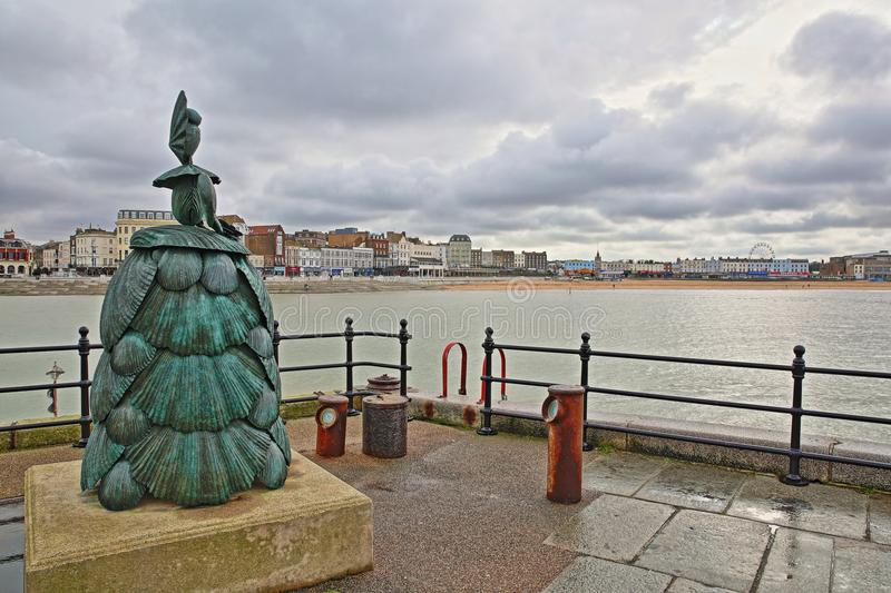 MARGATE, UK - FEBRUARY 3, 2018: Mrs Booth the Shell Lady sculpture by Ann Carrington on the Margate Harbor Arm, with the seafron. Mrs Booth the Shell Lady stock photos