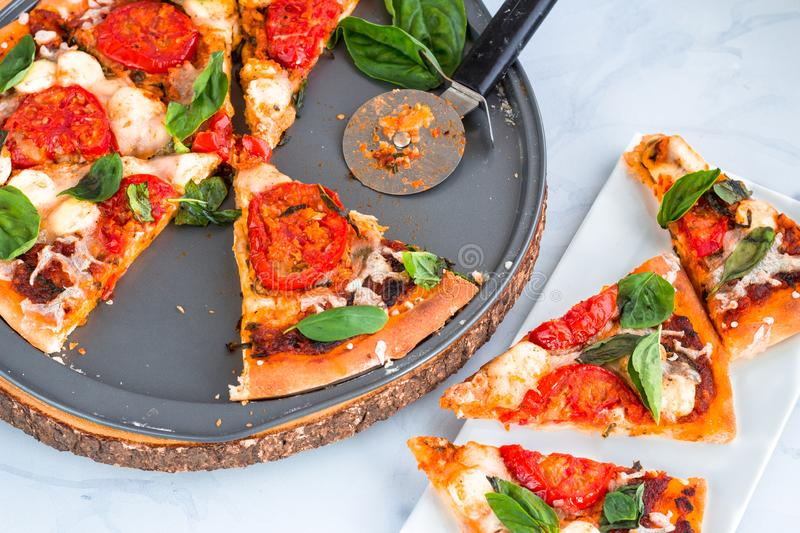 Margherita Pizza - a Thin crust Pizza on a Pizza Pan and Pizza Slices on a Platter royalty free stock photography