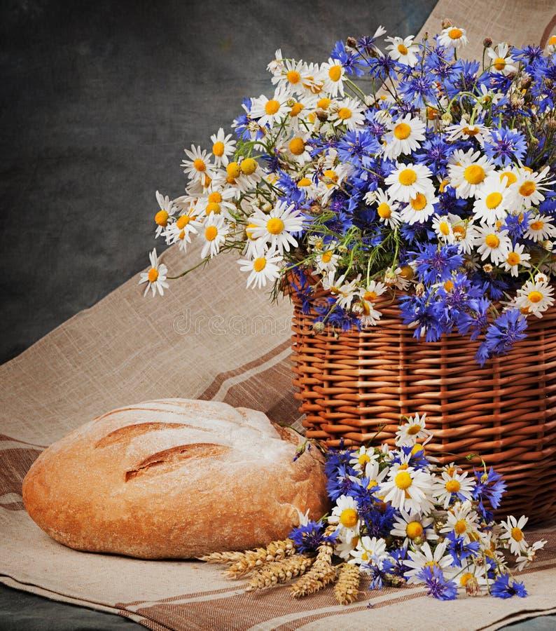Marguerites et bleuets toujours dans le panier Pain et lait sur t photographie stock