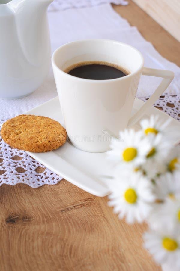 Marguerites et pissenlits, une tasse de caf? et un biscuit sur une table en bois photos stock