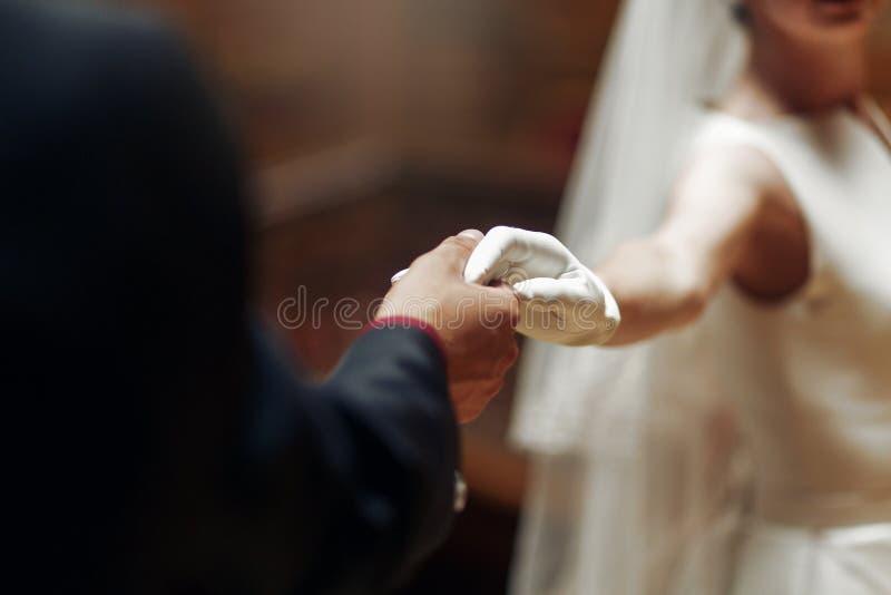 Marié élégant élégant tenant doucement la main des clos magnifiques de jeune mariée image stock