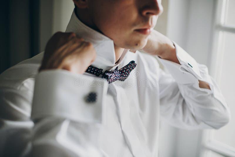 Marié élégant dans la chemise blanche mettant sur le noeud papillon près de la fenêtre dans la chambre d'hôtel Préparation de mat photo stock