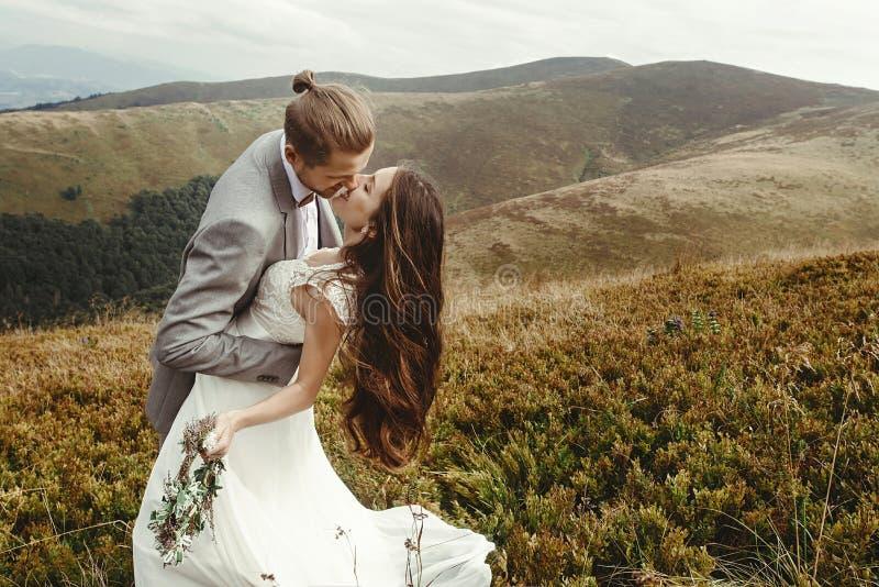Marié élégant embrassant la jeune mariée magnifique dans la lumière du soleil, mome parfait photographie stock libre de droits