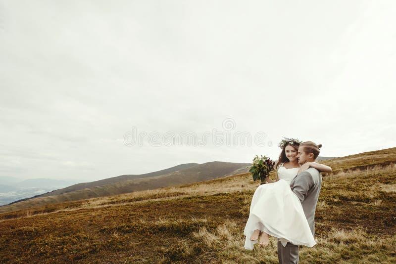 Marié élégant portant la jeune mariée heureuse et ayant l'amusement, mariage de boho photos stock