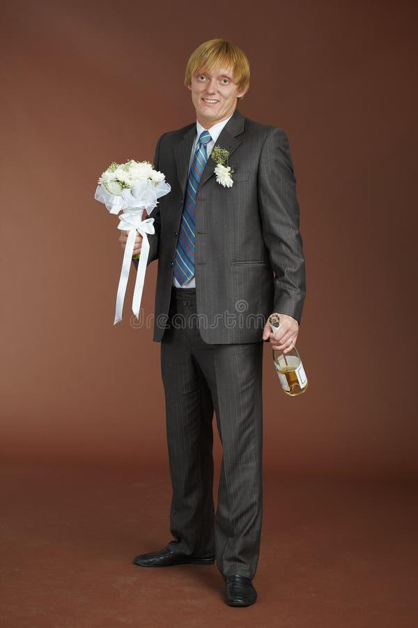 Marié avec le bouquet et bouteille de vin mousseux photographie stock