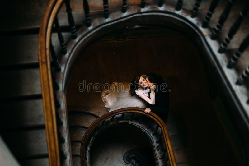 Marié beau embrassant la belle jeune mariée de sourire sur de vieux escaliers en bois à l'intérieur, vue supérieure image libre de droits