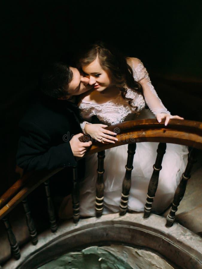 Marié beau heureux embrassant sa belle jeune jeune mariée sur les vieux escaliers en bois photographie stock