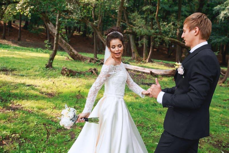Marié beau heureux et belle jeune mariée dans la robe blanche riant et dansant en parc photo libre de droits