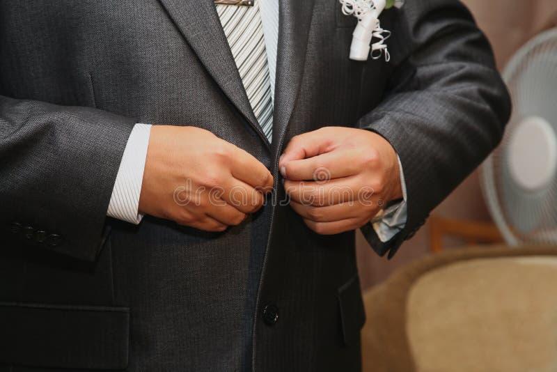 Marié boutonnant les boutons sur le costume image stock