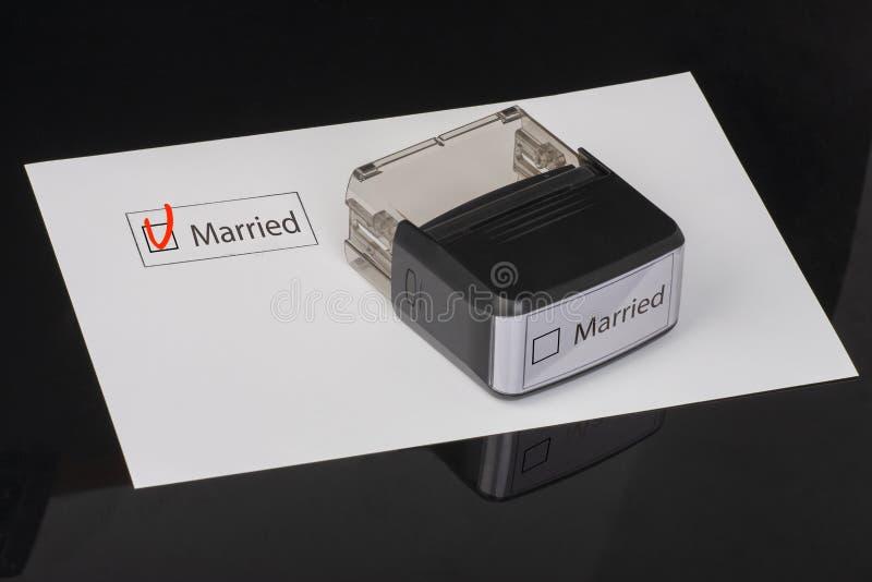 Marié - checkbox avec une croix sur le livre blanc avec la poinçonneuse en caoutchouc de poignée Concept de liste de contrôle photo stock