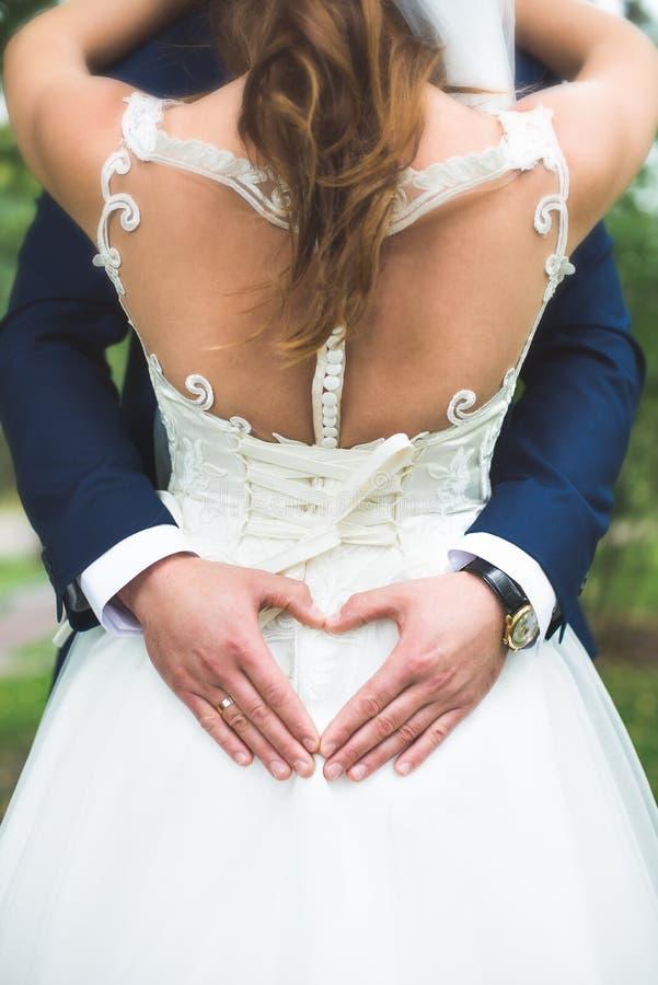 Marié créant la forme de coeur avec ses mains au dos de la jeune mariée Couples dans l'amour Fermez-vous vers le haut des mains L photo stock
