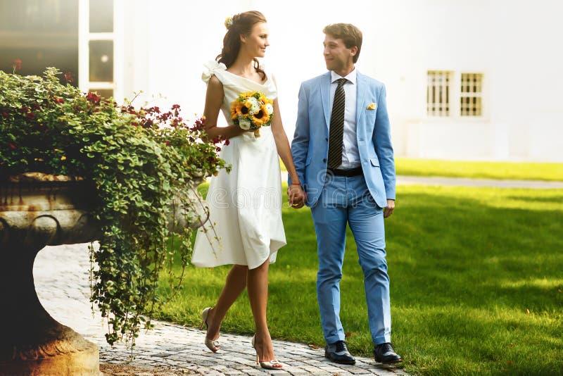 Marié dans le costume bleu et une jeune mariée dans une robe blanche marchant en m image stock