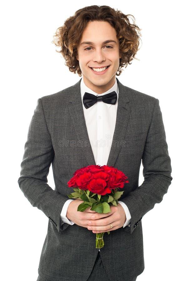 Marié dans le smoking posant avec un bouquet photo libre de droits