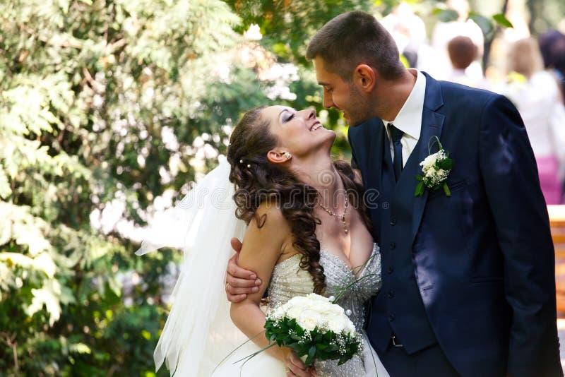 Marié dans une offre bleue de regards de costume à une jeune mariée heureuse image stock