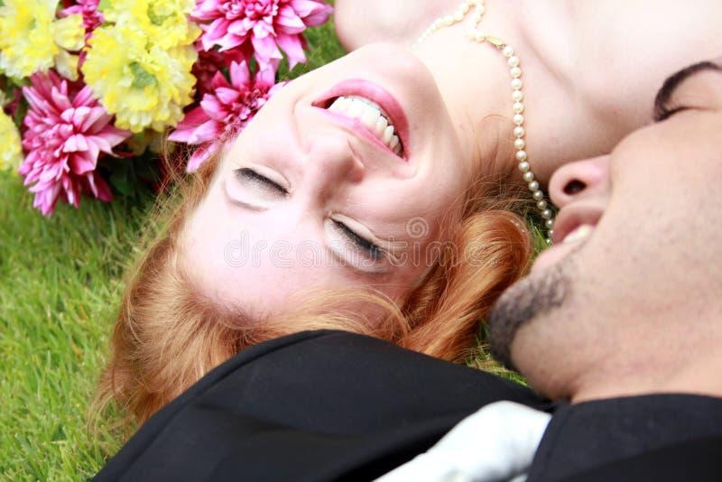 Marié de mariée se trouvant sur l'herbe photos libres de droits