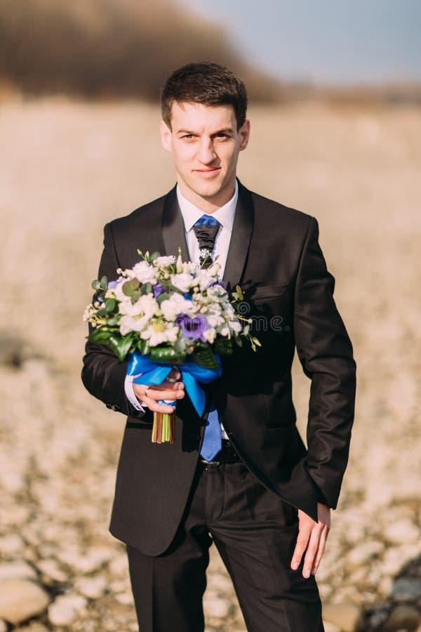 Marié de sourire élégant élégant de jeunes avec le bouquet des fleurs seul marchant sur la plage rocheuse photos stock