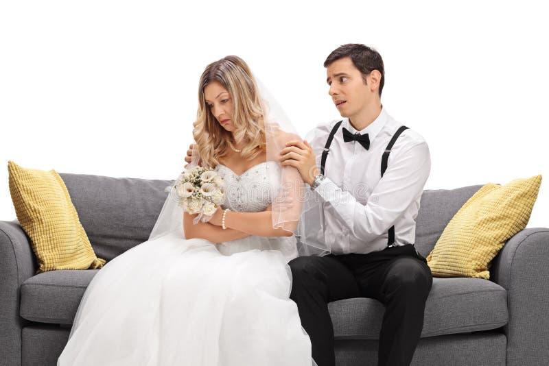 Marié essayant d'apaiser sa jeune mariée fâchée photographie stock libre de droits