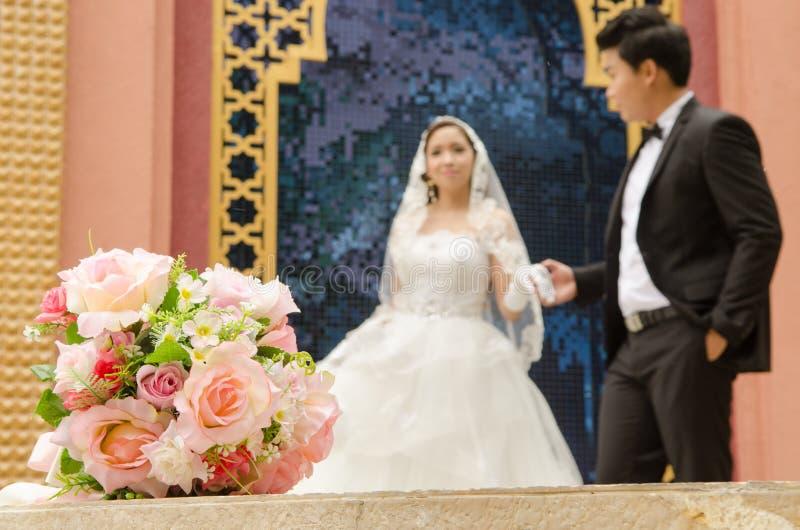 Marié et jeune mariée avec le bouquet de fleurs de mariage photo libre de droits