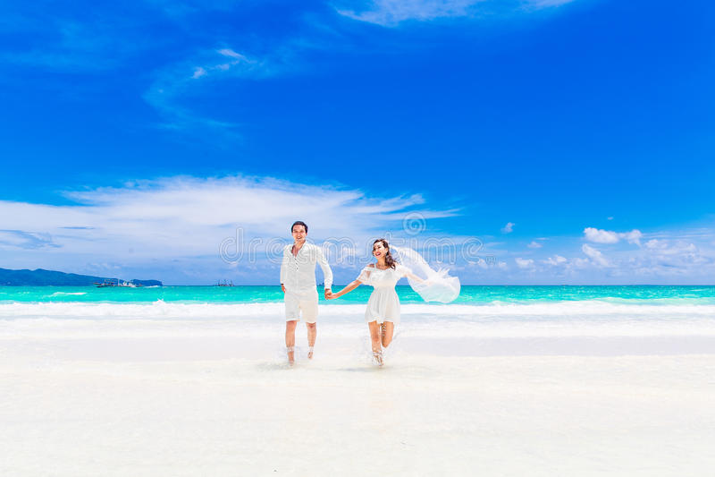 Marié et jeune mariée heureux sur la plage tropicale arénacée Mariage et h photographie stock libre de droits